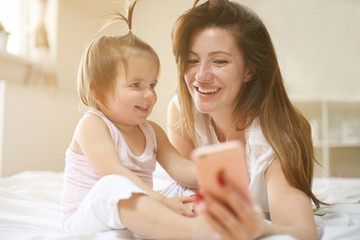 Mother with her little baby having fun in the bed. Using smart phone.