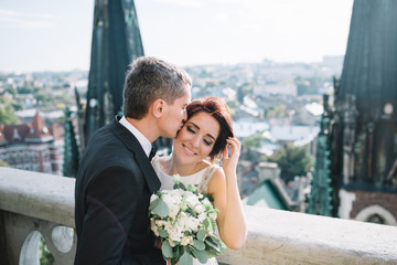 Groom kisses bride's head while she fixes her hair standing on the windy roof