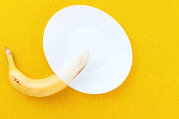 Half-cleaved yellow ripe bananas from the tropics on a white plate and yellow fabric background with space for text