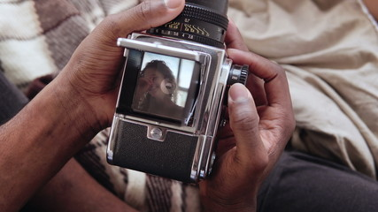 Close-up view of african man holding old photocamera, taking photo portrait beautiful woman. Multiracial couple on bed.