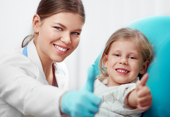Happy child in dentist chair with female doctor showing thumbs up.