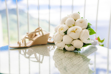 Wedding bouquet of peonies and bridal shoes