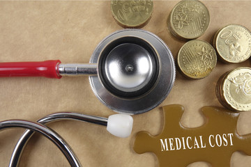 Medical concept with stethoscope,piece of puzzle and coins with HEALTH CARE conceptual text.