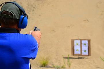 Man shooting pistol at targets at the range.