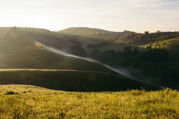 Landscape of hilly mountains in the fog. Green saturated meadows. Altai.