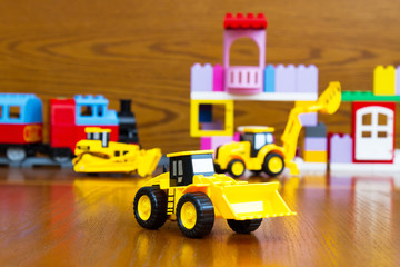 Children's construction equipment is yellow in the background of a toy building