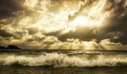 Wall Mural - Dramatic cloudscape over the sea with rays of sunlight and a foaming wave in the foreground, toned warm colors