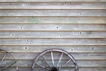 Old antique vintage wood wheel on a wooden texture wall