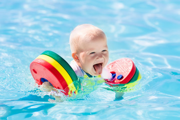 Little baby boy playing in swimming pool