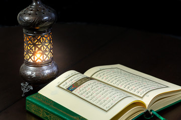Pages of holy book Qur'an with vintage lamp and dark background