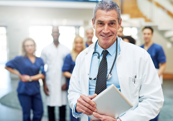 Doctor standing in front of medical team looking positive