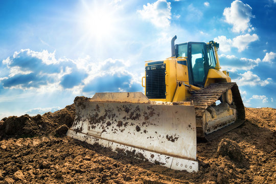Yellow excavator on new construction site, with the bright sun and nice blue sky in the background