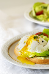Poached egg with running yolk on baguette slice with salad and tomatoes on a white plate, vertical, copy space