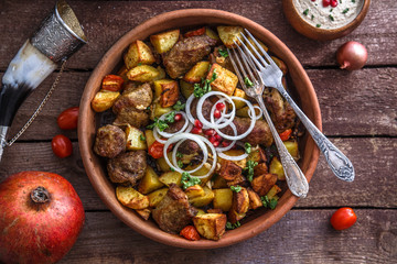 Big ceramic plate with roasted meat and potatoes with onion and wine. Traditional Georgian dish ojaxuri.