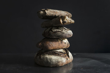 Stack of sourdough bread on table against black background