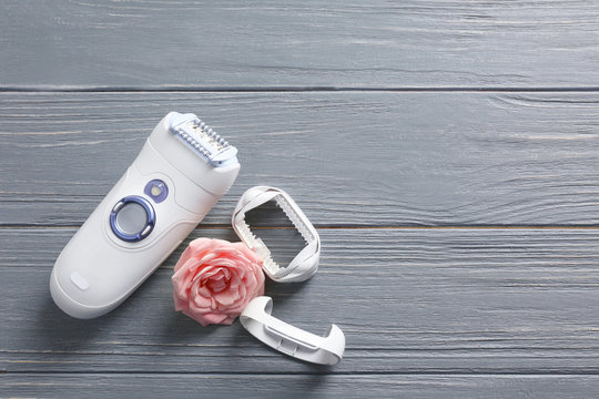 Modern epilator with accessories and flower on wooden background