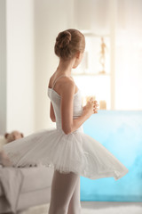 Young beautiful ballerina standing in her room at home