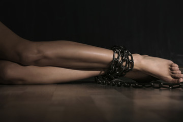 Woman with chained legs lying on floor in darkness