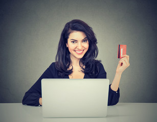 Internet shopping and payment. Woman showing credit card using laptop computer