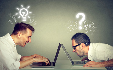 Two men using laptop computer one educated has bright ideas the other ignorant has questions