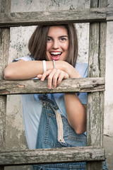 Portrait of a cheerful young woman leaning on a rustic wooden ladder