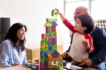 Family with child playing a toy block