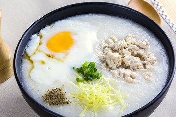 """Rice porridge is topping with ginger, spring onion, pepper, chicken, and onsen egg, Breakfast set on wooden table, spoon, pepper grinder. breakfast in Asia call """"congee"""""""
