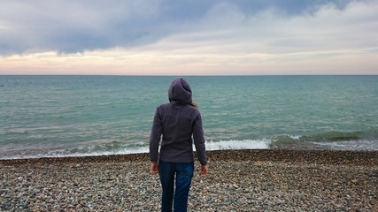 Rear view of alone young adult hipster girl standing on the beach, looking to sea, travel lifestyle
