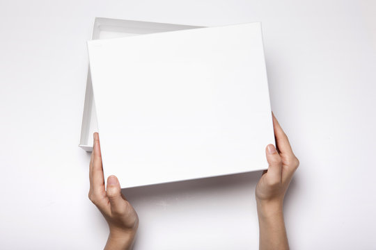 woman hand hold a white gift box isolated white.