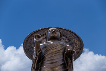Front of Bronze stand buddha statue, worm eye view