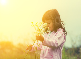 Happy little girl picking flowers in the meadow in sunny day