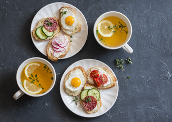 Mini sandwiches with cream cheese, vegetables, quail eggs, salami and green tea with lemon and thyme on a dark background, top view