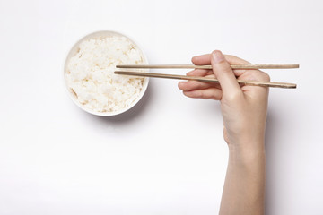 woman hand hold a chopstick with rice isolated white.