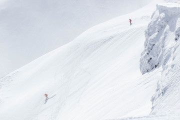 Freeride skier with rucksack running downhill in freeze motion of snow powder