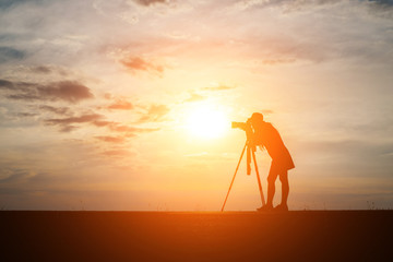 Silhouette of a photographer shoots a sunset.