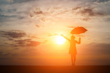Silhouette of woman holding umbrella on the beach and sunset.