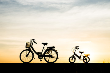 Two Silhouette vintage bicycle at sunset.