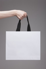 woman hand hold a shopping paper bag, grey background.