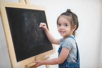 Smile girl draw cartoon with chalk and blackboard