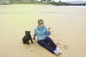 Senior woman doing a selfie with cellphone on the beach with dog