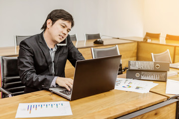 busy businessman working at office with laptop, mobile phone and documents.
