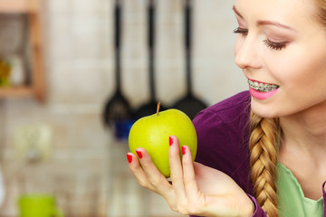 Woman young housewife in kitchen with apple fruit