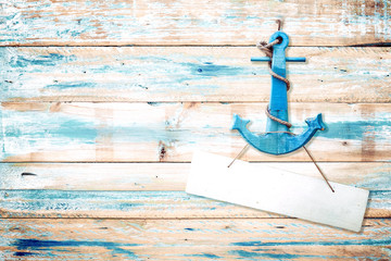 Vintage anchor on old wooden background with blue paint . vintage wood texture from beach in summer.
