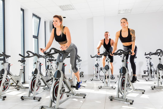 Group of fit people training at spinning class.