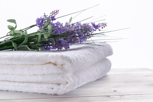 Photo of white towels resting on the table in the white backround.