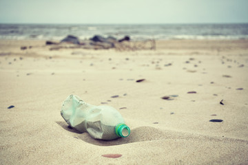 Retro stylized picture of an empty green plastic bottle left on a beach, selective focus, environmental pollution concept picture.