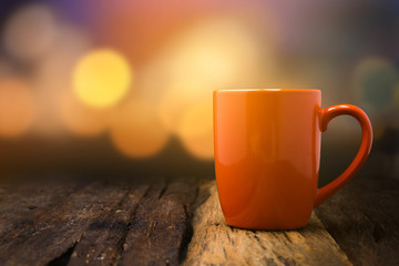 Orange ceramic empty mug on old wooden table top with copy space and bokeh background
