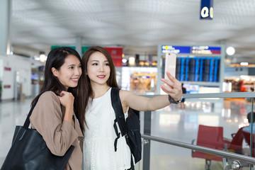 Girls Friends taking selfie in airport
