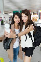 Young women taking selfie at airport