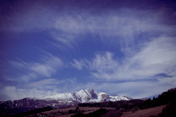 Photo depicting a beautiful moody frosty landscape. European alpine mountains with snow peaks on a blue sky background.